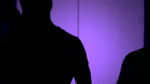Men And Women Walking In Front Of The Purple Light stock footage