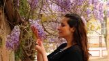 Beautiful Girl Smelling Flowers On The Street stock footage