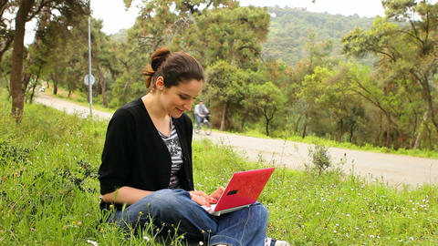 beautiful girl using computer in countryside, bicycles passing behind Footage