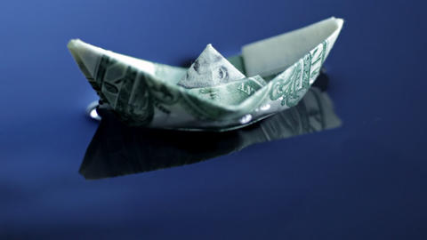 Origami Boat Made Of Dollar Bill Floating stock footage