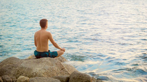 Young Man Practicing Yoga. Sits In A Lotus Positio stock footage