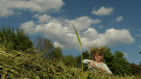 Little Girl Weaves A Wreath Of Grass On The Field stock footage