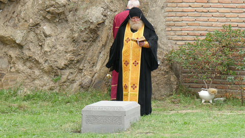 Orthodox Priest Celebrating Ceremony At Burial In stock footage