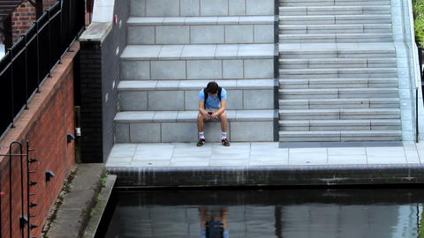 Boy With A Cell Phone Sitting By The Canal stock footage