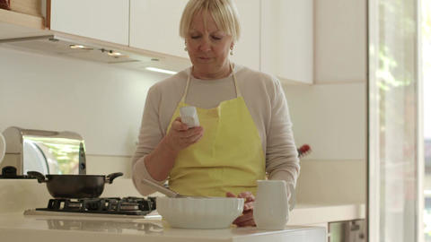 Happy Senior Woman At Home, Cooking In Kitchen And Using Telephone stock footage