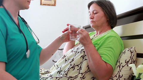 Home Caregiver Giving Medicine To Senior Woman stock footage