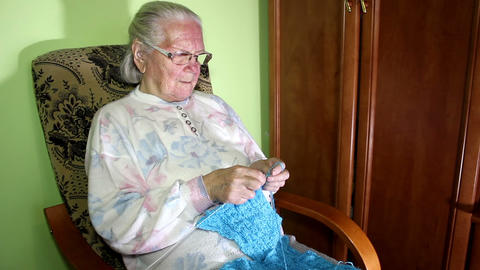Elderly woman sitting in a chair and knitting Footage