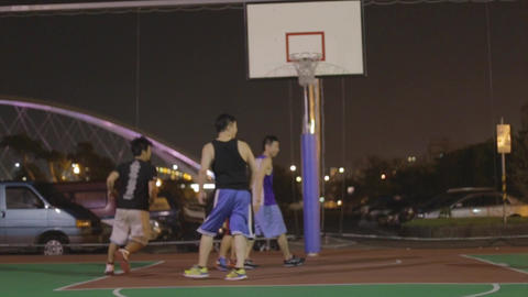 Asian Men Play Basketball At The Key stock footage