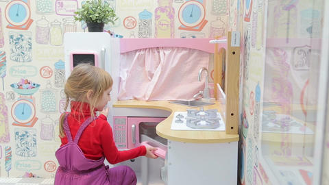 Girl playing with a toy kitchen with microwave Footage