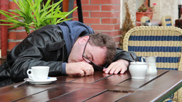 Drunk Or Tired Man Wakes Up In Outdoor Cafe stock footage