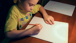 Pretty little girl drawing with concentration Footage