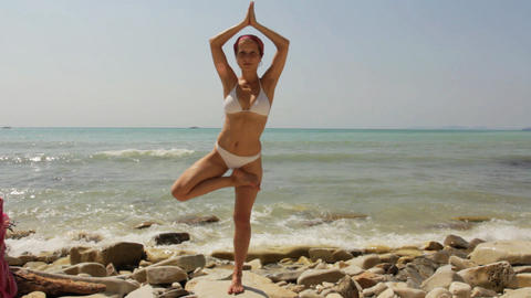 Young Woman Doing Yoga Exercises On Beach stock footage