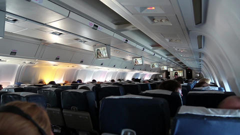 People watching a movie aboard an airplane Boeing 767 Footage