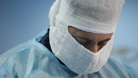 Close-up of a surgeon and then hands during insertion of needle into the vein ビデオ