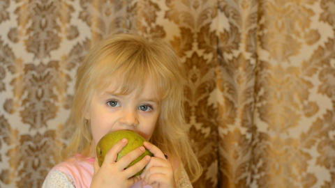 Little Girl Emotionally Taking A Bite Out Of A Fresh, Organic Pear stock footage