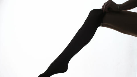 Lady Puts On Stockings In Silhouette stock footage
