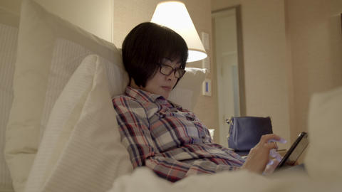 Asian Woman Looking At Photos On Cellphone In Hotel Room . 4K UHD stock footage