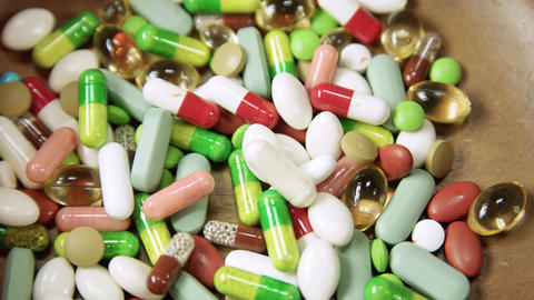 Multi Colored Pills And Tablets Poured Into Bowl stock footage