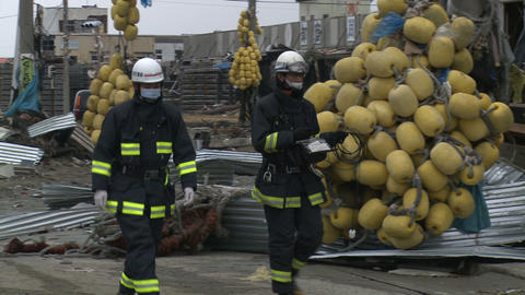 Japan Tsunami Aftermath - Fire Crew Walks Through Destroyed Port stock footage