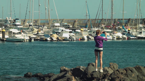 Long Shot Of Blond Girl Model Shooting Panoramic Video Photo A Of Yacht Club OE stock footage