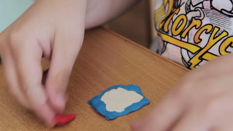 Child Moulds From Plasticine On Table stock footage
