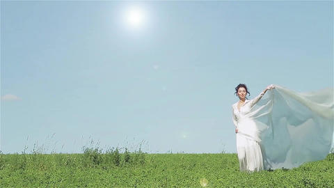Girl In White Dress Walking On Green Field With A Shawl Which Is Fluttering In T stock footage