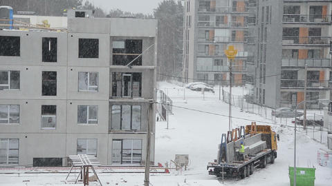 Crane lift block house part and workers work in heavy blizzard Footage