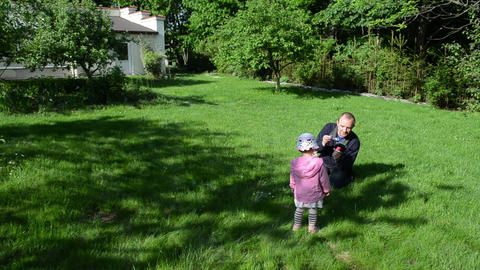 Father Blowing Soap Bubbles In Garden. Girl Clapping Hands stock footage