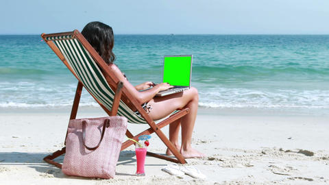 Pretty Brunette Using Laptop On Deck Chair stock footage