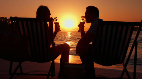 Couple Drinking Couple During The Sunset On The Beach stock footage