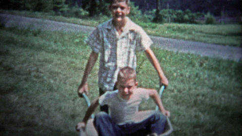 TENNESSEE, USA - 1953: Older brother pushing around kid in a wheelbarrow for sum Footage