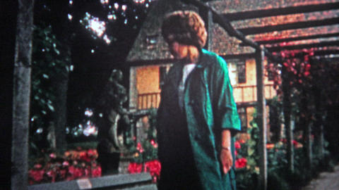 HAMBURG, GERMANY - 1966: Women walking through red flower conservatory garden du Footage