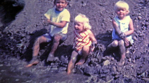 1969: Kids playing in mud made from construction project Footage