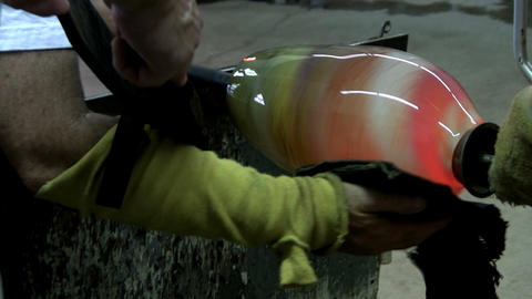 Glass Artist Uses Puffer And Kevlar Pad In Shaping Mouth Of Spiral Colored Vase stock footage