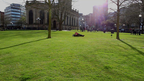 A Man Lying On The Grass Taking A Rest In A Public Square stock footage