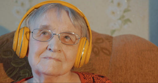 Senior woman in headphones listening to music Footage