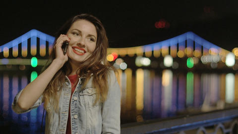 Girl Talking on the Phone at Night in the City with Illuminating Background Brid Footage