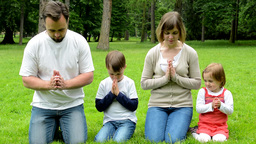Family (middle Aged Couple In Love, Boy And Girl) Pray In Park (family Kneeling  stock footage