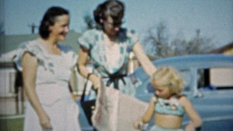 1953: Mom Reading Paper Helping Baby And Aunt Walking stock footage