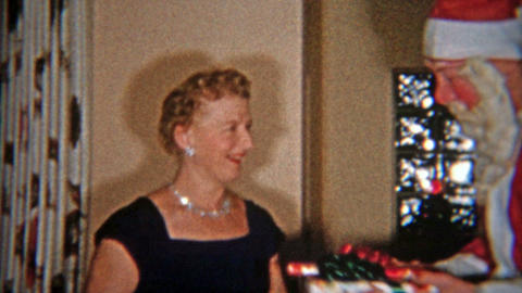 1953: Creepiest Santa Claus Mask Ever Giving Gifts To Family stock footage