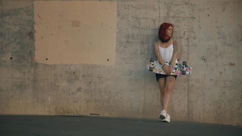 Tattooed Red Head Woman Stands In A Concrete Wall With His Skateboard stock footage