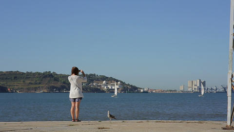 Girl Takeing Picture And Looking At The River In Portugal Belem Embankment stock footage