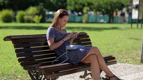 Young Beautiful Woman Holding Mobile Phone In Hand And Sitting On The Bench In T stock footage