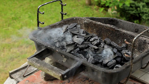 Blowing Smoke Rising From A Charcoal Placed In Grill Arranged In A Garden On Win stock footage