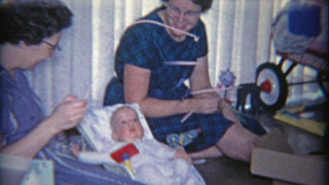 1958: Women Mesmerizing Baby With Butterfly Mobile Toy stock footage