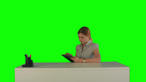 Business Woman Sitting In Her Office Using A Tablet Computer On A Green Screen stock footage
