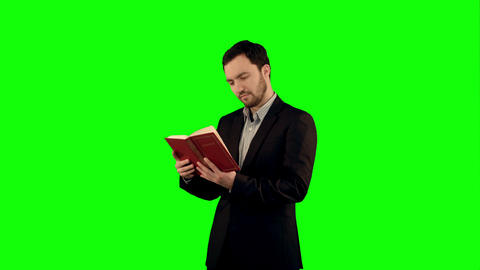 University Student With Book On Laptop On A Green Screen, Chroma Key stock footage