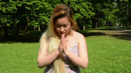 young attractive asian woman prays and nods her head in the park - close up Footage
