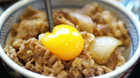 Delicious Eating Raw Egg Yolk On Food. Japanese Beef Over Rice. Poached Runny Eg stock footage
