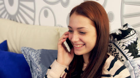 Pretty Young Girl Talking On Phone In Bed stock footage